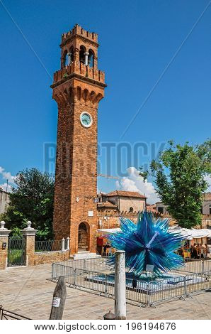 Murano, Italy - May 08, 2013. View of clock tower made of bricks and a star shape glass sculpture at Murano, a little town on top of islands near Venice. Located in the Veneto region, northern Italy
