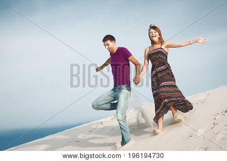 happy couple running from the mountain. couple on romantic travel honeymoon vacation summer holidays romance.
