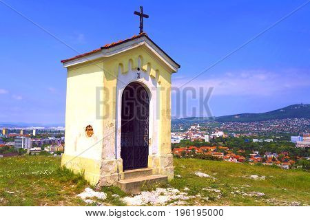 Catholic chapel on a hill with a city in the background