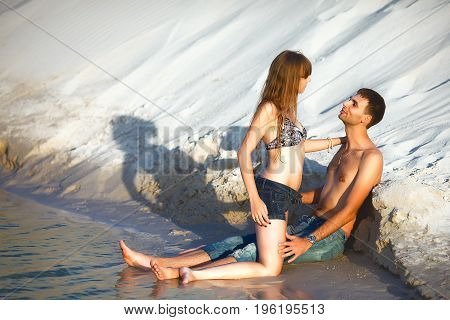 in love couple on romantic travel honeymoon vacation summer holidays romance. in love girl and handsome man kissing and embracing on ocean shore