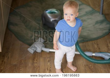 Baby boy cleaning up the kitchen with hoover.
