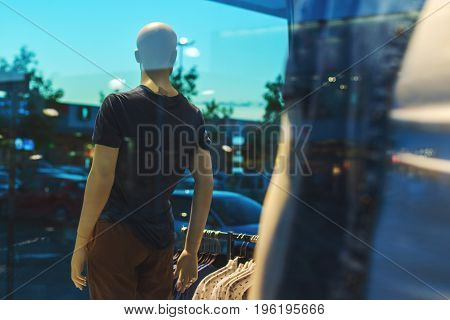 Storefront boutique mannequin with clothes on sale male figure portrait selective focus