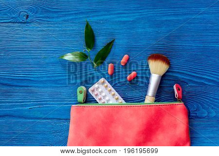 Cosmetic bag with contraceptive pills on blue table background top view.