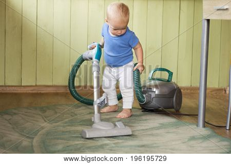 Cute toddler cleaning up the kitchen with hoover.