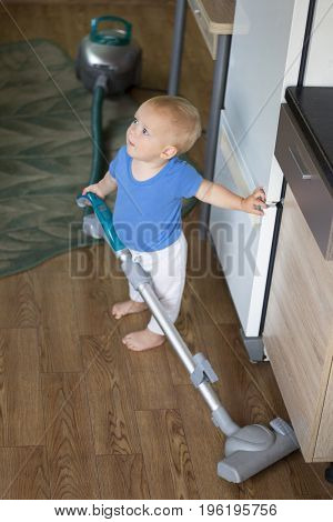 Adorable baby boy cleaning up the kitchen with hoover.