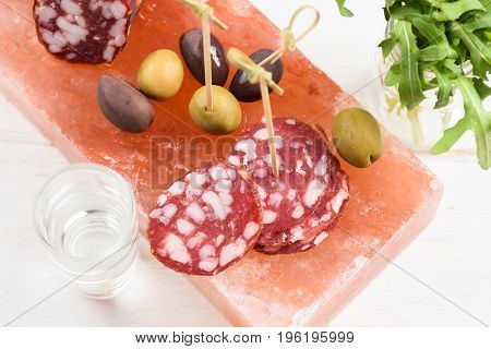 Salami calamata and green olives fresh arugula as appetizer served with vodka shot on pink hymalayan salt block on white background overhead view