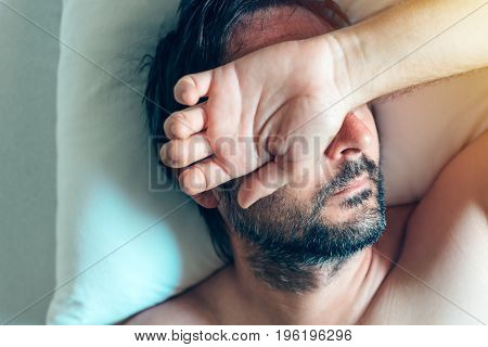 Morning depression and midlife crisis of a man in his 40s lying in bed in morning with symptoms like extreme sadness frustration anger and fatigue.