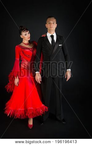 couple in love ballroon dance couple in red dress and black tuxedo on black background
