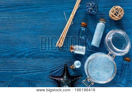 Dead sea cosmetics. Sea salt, blue clay and lotion on blue wooden table background top view.