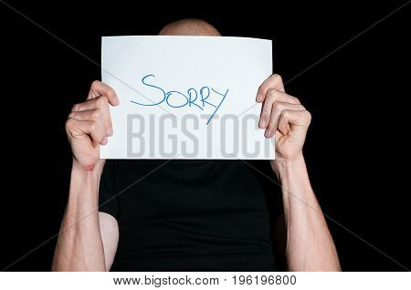 Sorry. Desperate man beg for forgiveness by holding paper with sorry sign.  Dark image. Loneliness. Sadness. Regret.