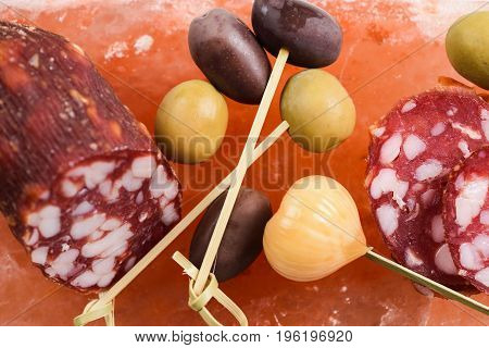 Green and calamata olives pickled garlic and salami served on hymalayan pink salt block overhead view