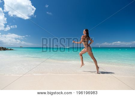 Girl in sexy swimsuit running on sea beach with white sand turquoise water and blue sky on sunny day on natural environment. Sun tanning bathing. Summer vacation. Rest relaxing active leisure