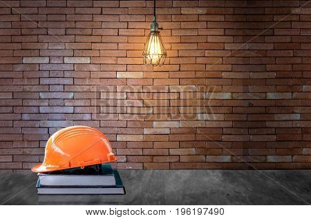 Education engineer concept.Orange helmet on book and background brick wall with bulb lights lamp