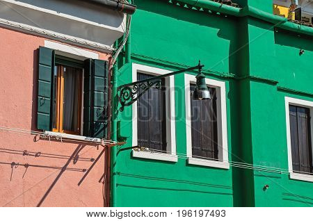 Close-up of windows on colorful walls and lamp on sunny day in Burano, a gracious little town full of canals, near Venice. Located in the Veneto region, northern Italy