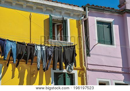 Close-up of windows on colorful walls and clothes hanging on sunny day in Burano, a gracious little town full of canals, near Venice. Located in the Veneto region, northern Italy