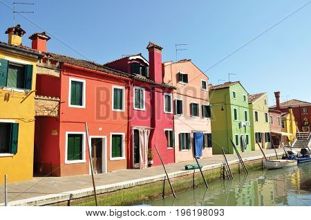 Panoramic view of colorful buildings and boats in front of a canal, in a sunny day at Burano, a gracious little town full of canals, near Venice. Located in the Veneto region, northern Italy