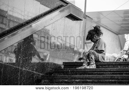 Homeless child eating on the stairway in the street. Social documentary street. Black and white. September - 16. 2016. Novi Sad, Serbia. Editorial image.