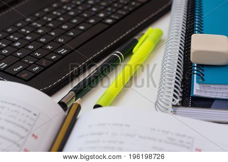 Laptop tablet keyboard opened textbook with math formula pencil stack of school notebooks highlighter on white desktop learning studying education college