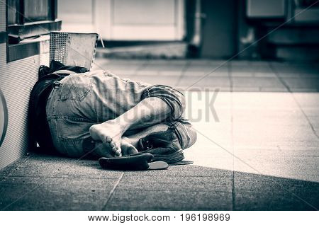 Homeless barefoot man sleep on the street, in the shadow of the building. Social documentary.