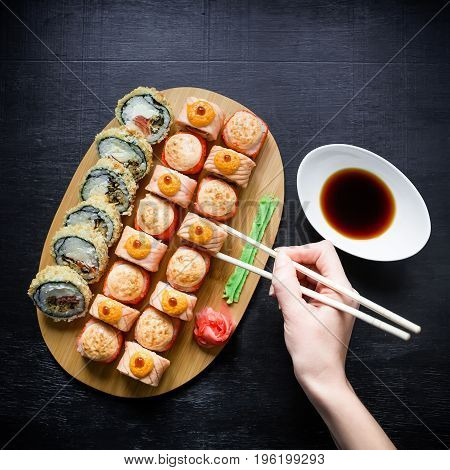 Traditional Japanese food - sushi rolls and sauce and hand with chopsticks on a dark background. Top view. Flat lay