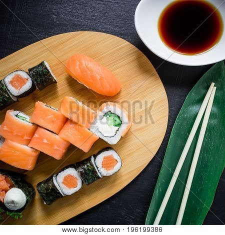 Japanese food, catering, roll plate or platter set. Sushi roll with chopsticks, ginger, soy sauce, wasabi at dark background. Top view. Flat lay