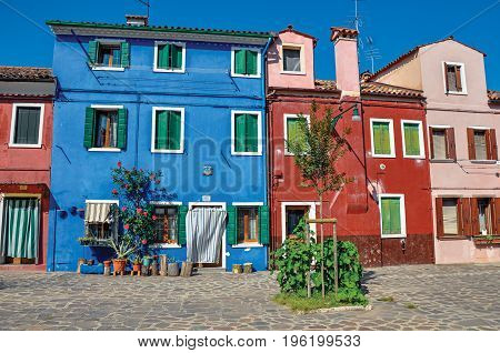 Burano, Italy - May 08, 2013. Overview of colorful terraced houses on sunny day in Burano, a gracious little town full of canals, near Venice. Located in the Veneto region, northern Italy