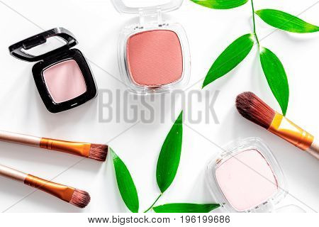 Make up brushes set, eyeshadow and blush on white table background top view.