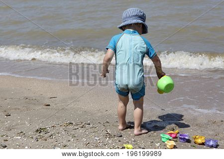 Child with toy watering can on the beach