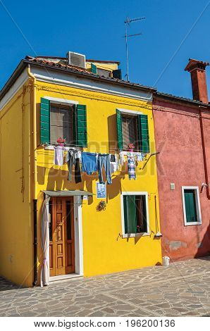 Burano, Italy - May 08, 2013. View of colorful terraced houses and clothes hanging in an alley on sunny day in Burano, a gracious little town full of canals, near Venice. Veneto region, northern Italy