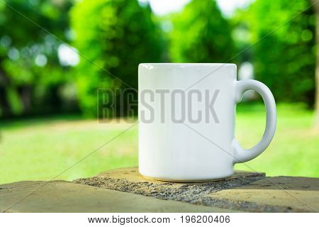 White mug mock up empty space for artwork text standing on stone outdoors green grass trees sky in the background soft sunlight nature
