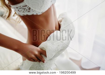 Sexual bride standing near the window in white lace lingerie is putting on her white wedding dress in luxury room. Close-up. Morning preparation