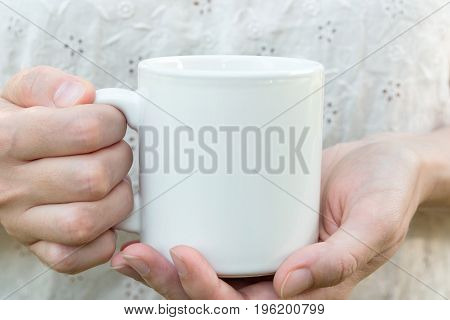 Young caucasian woman holding a white mug mock up blank space for text artwork hands linen shirt natural authentic kinfolk style soft light