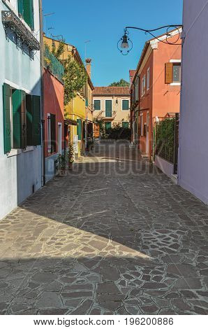 Overview of colorful terraced houses, lamp and bushes in an alley on sunny day in Burano, a gracious little town full of canals, near Venice. Located in the Veneto region, northern Italy