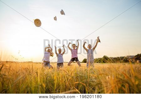 Four young children jumping up in the field throwing straw hats in the air,wearing casual summer clothes.
