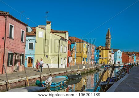 Burano, Italy - May 08, 2013. Colorful buildings, tower, people and boats in front of a canal at Burano, a gracious little town full of canals, near Venice. In the Veneto region, northern Italy