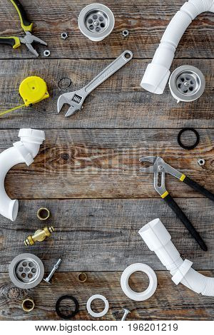 Plumber tools on wooden background top view.