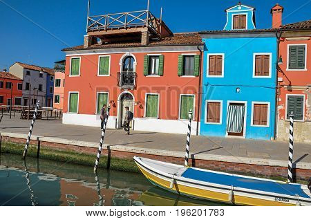 Burano, Italy - May 08, 2013. Colorful buildings, people and boats in front of a canal at Burano, a gracious little town full of canals, near Venice. Located in the Veneto region, northern Italy