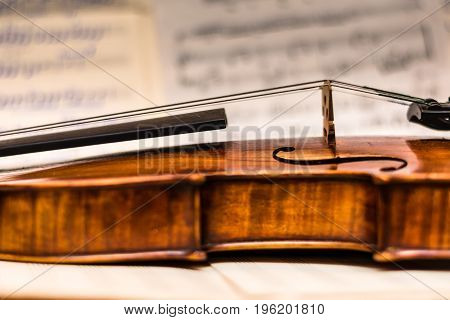 The part of very rare and old violin on blurry background with musical notes with some ancient song.