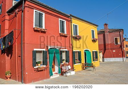 Overview of colorful buildings and clothes hanging in a blue sunny day, in front of a canal at Burano, a gracious little town full of canals, near Venice. Located in the Veneto region, northern Italy