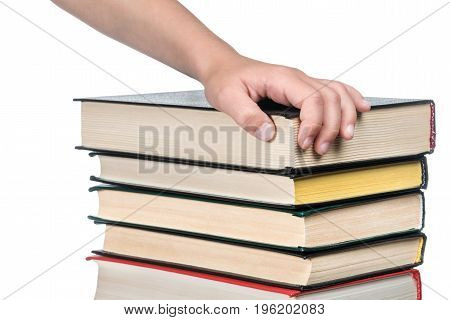 Child hand on a pile of thick books, close-up, isolated on a white background
