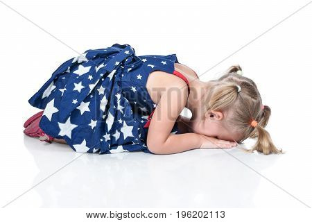Little girl in a beautiful dress is sitting on the floor with her head resting on her palms and crying, isolated on a white background