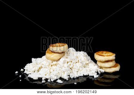 Heap of cottage cheese and delicious cheese cakes made out of it isolated on a black background