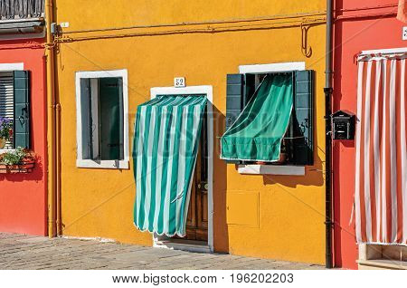 Burano, Italy - May 08, 2013. Close-up of colorful houses and doors with cloth on a sunny day in Burano, a gracious little town full of canals, near Venice. Located in Veneto region, northern Italy