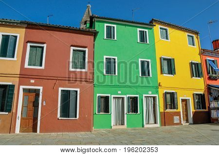 Burano, Italy - May 08, 2013. Overview of colorful terraced houses in alley on a sunny day in Burano, a gracious little town full of canals, near Venice. Located in the Veneto region, northern Italy
