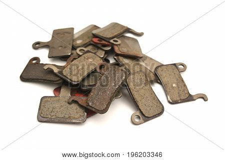 a heap of used bicycle brake pads isolated on white