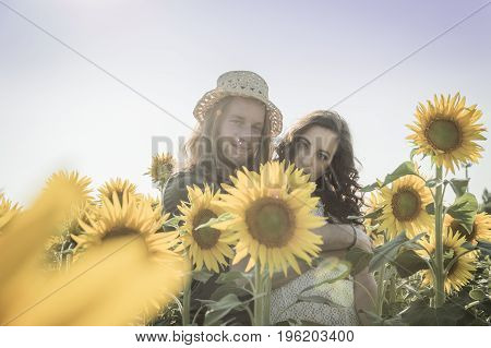 Young happy and romantic caucasian couple at sunflowers field