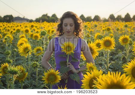 Young caucasian woman with long hairs among sunflowers field