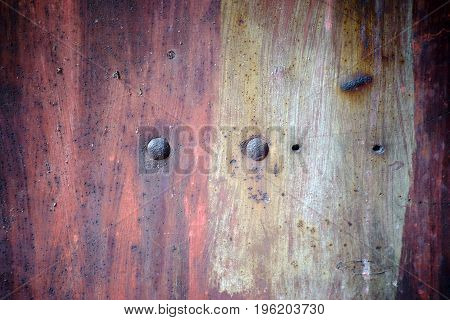 The closeup of a rusty metal surface with rust bubbles and rusty rivets.