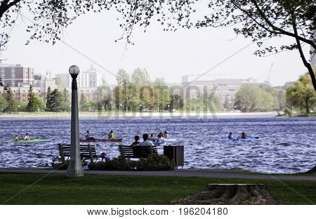 Ottawa, Ontario, May 18, 2017 -- Wide view of people paddling and enjoying the Rideau Canal with a walking path in the foreground and buildings in the background on a bright sunny day in May at the International Tulip Festival in Ottawa, Ontario.