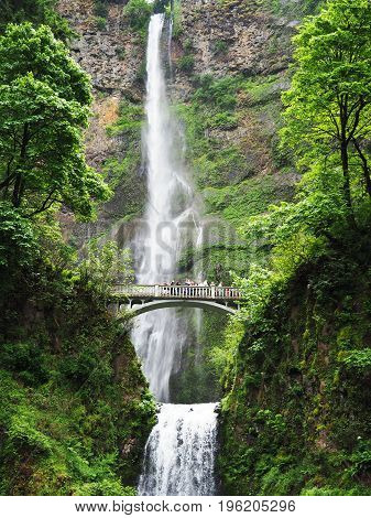 Tourists look up at a huge waterfall